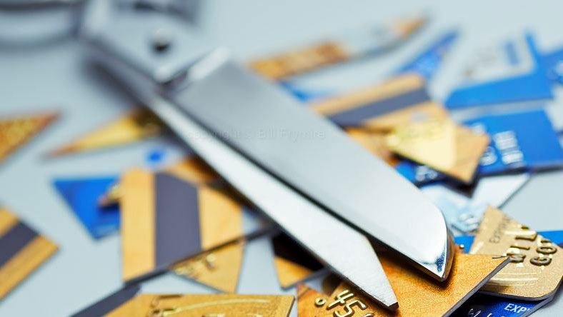 A pair of scissors on top of a pile of cut up credit cards