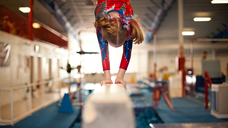 A young female gymnast doing a handstand on a balance beam