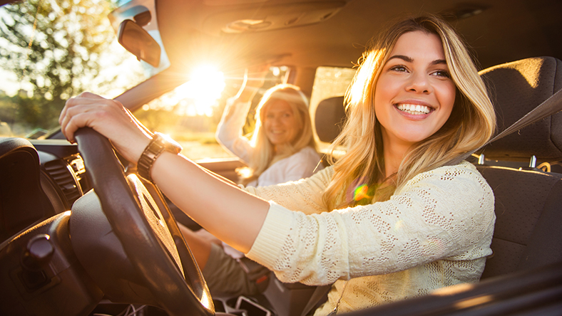 Two women looking out the driver's side window smiling with a sunset behind them
