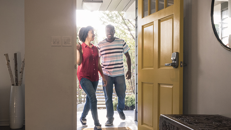 A young couple entering their home