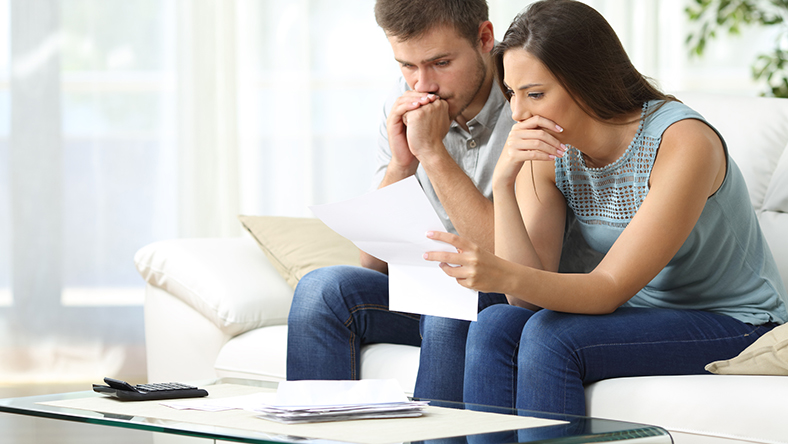 A concerned couple reviewing documents sitting on the couch