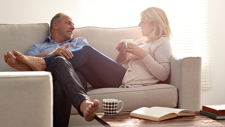 A man and woman sitting on a couch having a candid conversation