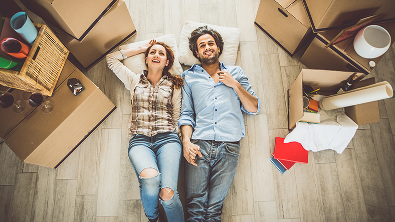 A couple sitting on the floor holding hands surrounding by moving boxes