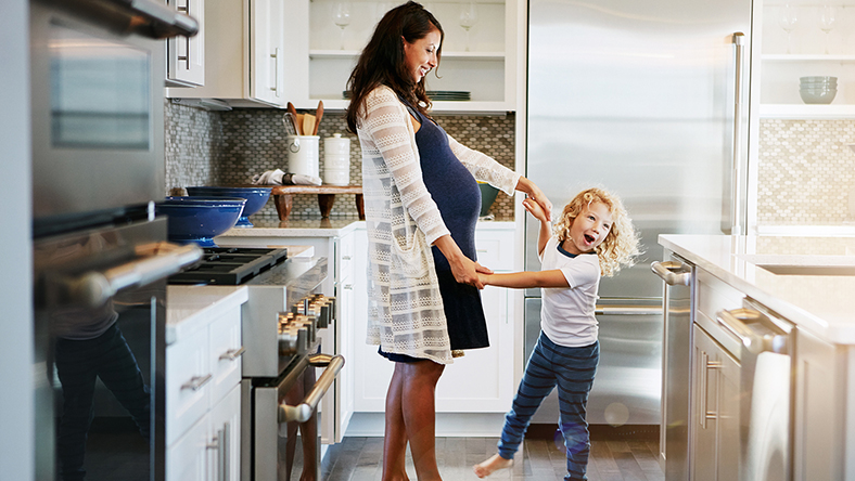 A pregnant woman dancing with a child in the kitchen