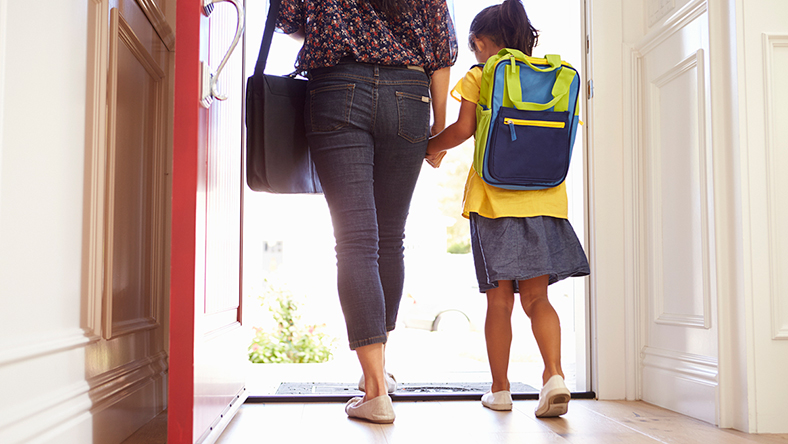 Woman holding hands with her child leaving the house for school