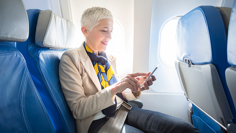 Woman looking at her phone sitting in an airplane seat