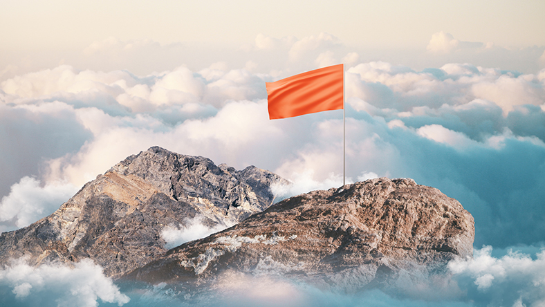 A flag on top of a mountain above the clouds