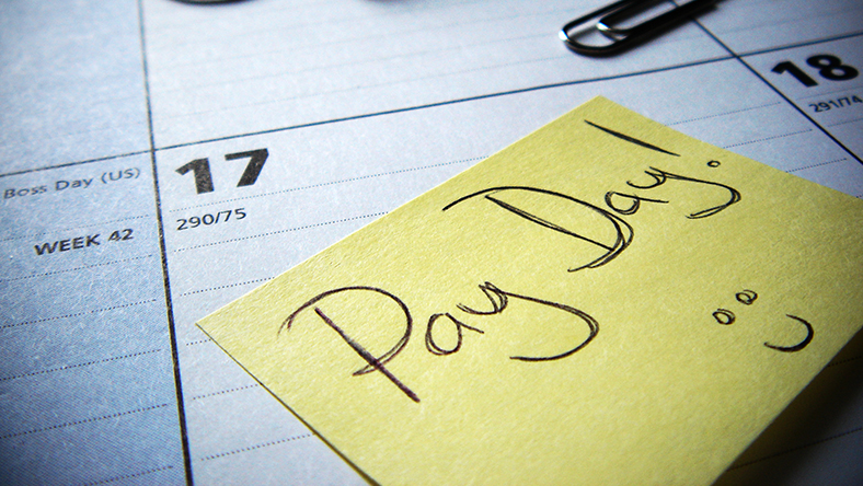 Post-it note on a calendar marking pay day