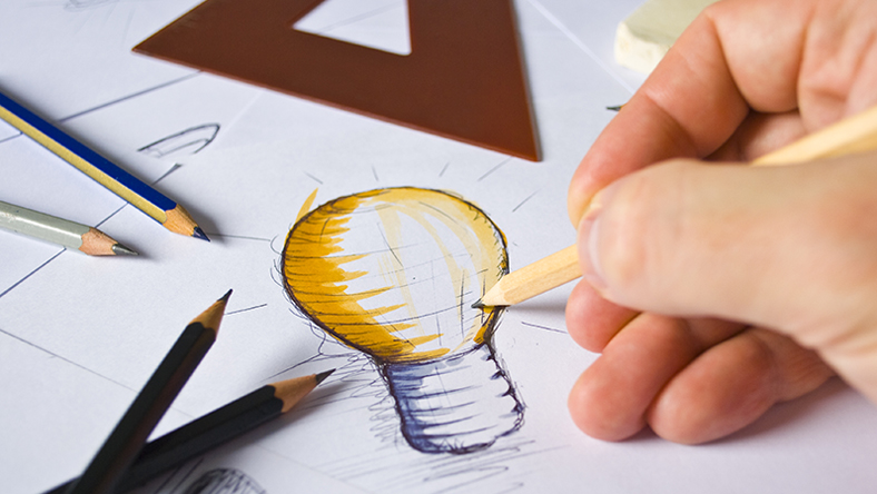 Person drawing a lightbulb on paper