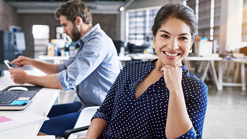 Woman smiling in an open office environment