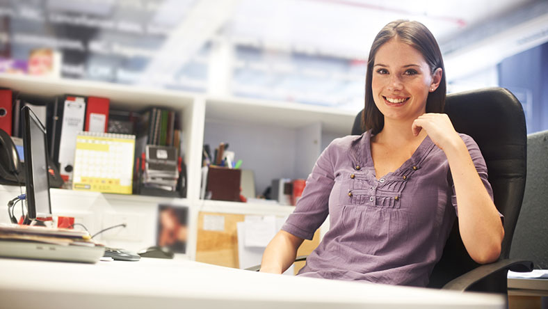 Woman sitting at her office desk smiling