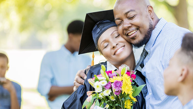 A woman in her graduation outfit hugging her husband and holding flowers